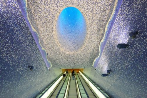 "People walk in the ""Cathedral"" with the Crater of Luz by artist Oscar Tusquet Blanca in the Toledo subway station as part of the ""Art Station Line 1"" project on November 5, 2012 in Naples.  AFP PHOTO / MARIO LAPORTA"